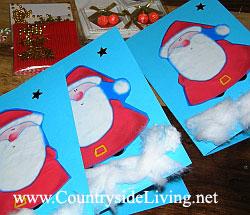 """Самодельные детские открытки моей дочери. Цветная плотная бумага, вырезанные изображения Деда Мороза из новогодней упаковочной бумаги, вата (""""снег"""") и звездочки"""
